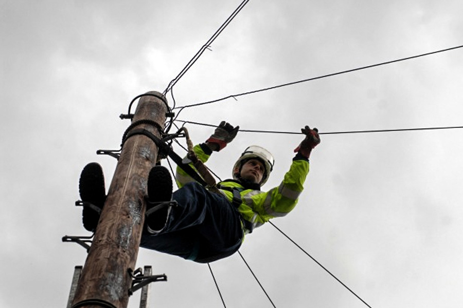 An Openreach engineer on top of telephone pole carrying out repairs