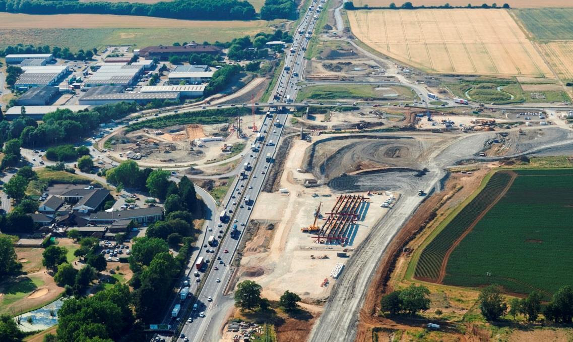 Caption: The Bar Hill junction on the A14 in Cambridgeshire, July 2018. The abutments for the two new bridges can be seen just south of the existing bridge and further down on the right of the road, the bridge decks can be seen being built.