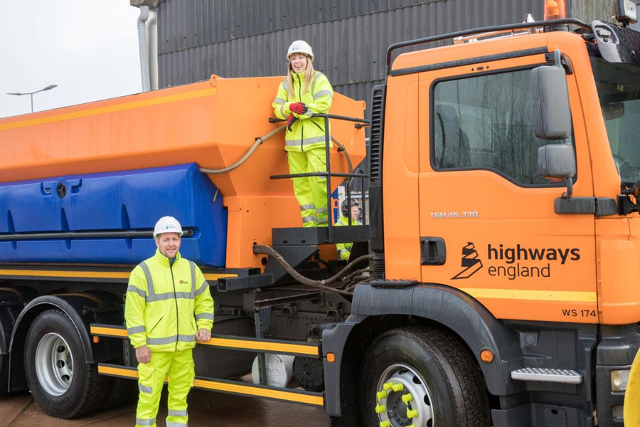 Caption: Karen and Neil next to one of the gritting machines being used to keep motorways moving this winter