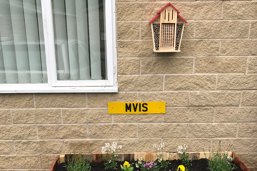 Above the flower bed the bee house proudly sits
